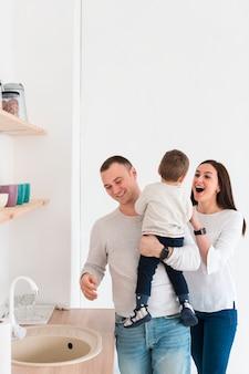 Felices padres con niño en la cocina