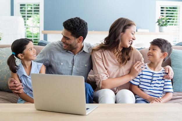 Felices padres y niños sentados con el brazo alrededor en la sala de estar