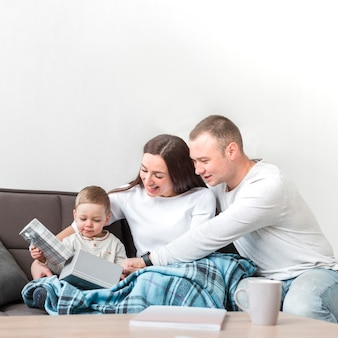Felices padres en el sofá con niño