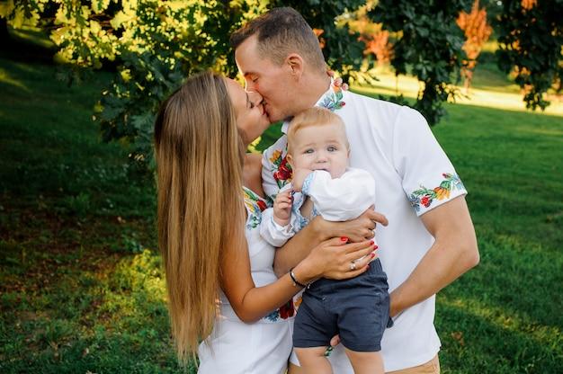 Felices padres sosteniendo en las manos a un bebé vestido con el bordado y besándose