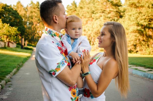 Felices padres sosteniendo en las manos un bebé vestido con la camisa bordada