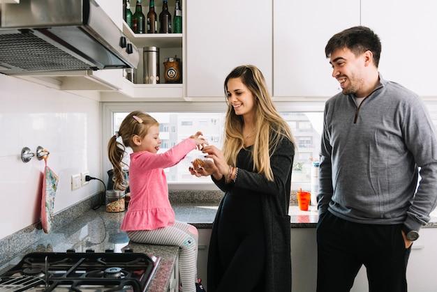 Felices padres con su hija en la cocina