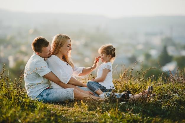 Los felices padres y su pequeña niña descansan en el césped en un hermoso día de verano
