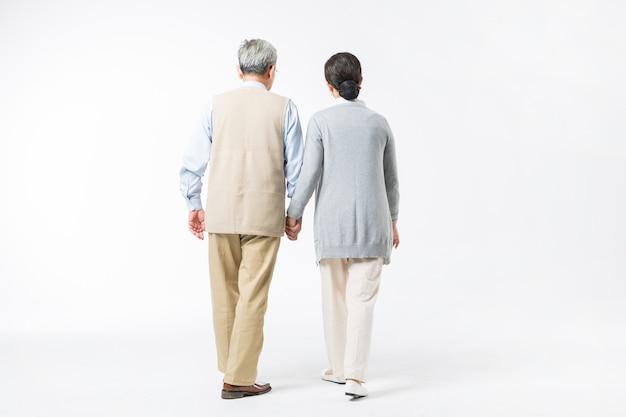 Felices parejas de ancianos caminando de la mano