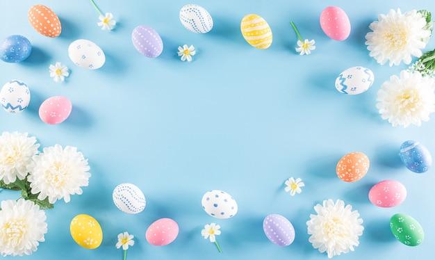 Felices pascuas coloridos de los huevos de pascua con flores en azul pastel