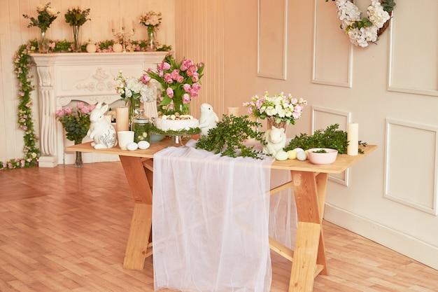 ¡felices pascuas! decoraciones navideñas. hermosa mesa festiva de pascua con conejito, flores y huevos. tema de color de primavera, espacio de copia. plantilla de tarjeta de felicitación de pascua. cocina interier.