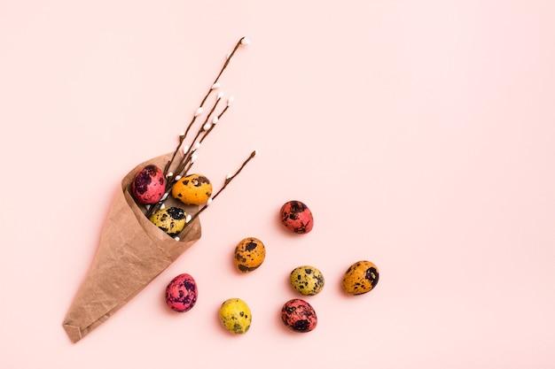 Felices pascuas. huevos de codorniz pintados y sauce en papel de regalo sobre fondo rosa