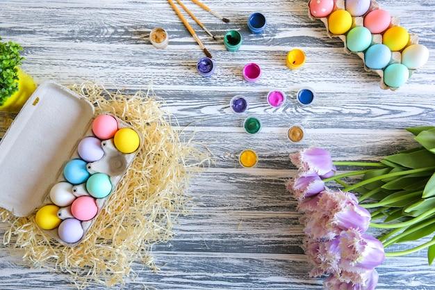Felices pascuas. huevos de colores en la cesta. decoración de mesa para vacaciones. vista superior.