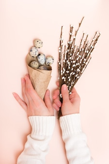 Felices pascuas. manos femeninas sostienen una bolsa de huevos de codorniz y un ramo de sauce sobre un fondo rosa