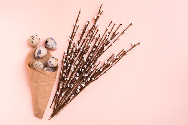 Felices pascuas. paquete con huevos de codorniz y ramo de sauce sobre fondo rosa