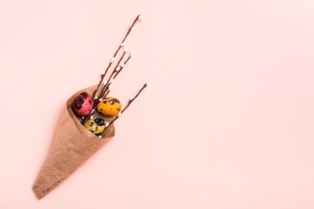 Felices pascuas. ramo de huevos de codorniz pintados y ramas de sauce envuelto en papel marrón sobre fondo rosa