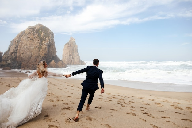 Felices recién casados agarrados de sus manos están corriendo por la playa en el océano atlántico