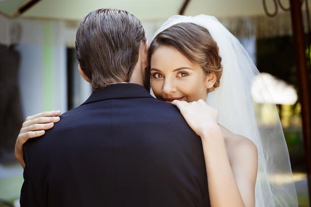 Felices recién casados hermosos sonriendo, abrazándose en la cafetería al aire libre.
