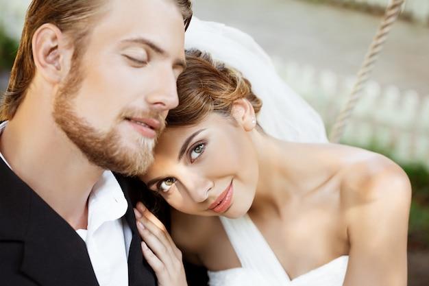 Felices recién casados hermosos en traje y vestido de novia sonriendo, disfrutando.