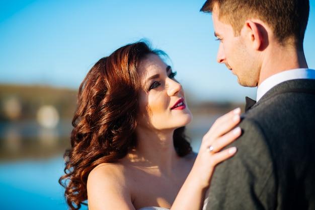 Felices recién casados sonrientes caminando al aire libre, besándose y abrazándose el día de su boda