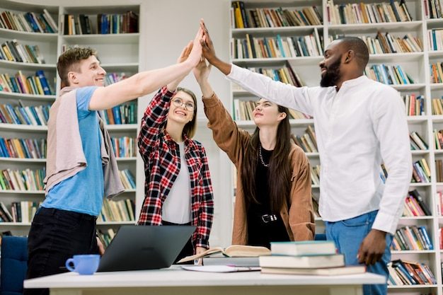 Felices satisfechos atractivos jóvenes multiétnicos, estudiantes o compañeros de trabajo, de pie a la mesa con libros