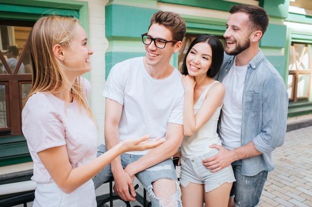 Felices y satisfechos, hombres y mujeres jóvenes están parados juntos en un edificio verde
