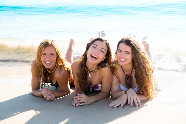 Felices tres amigas chicas tumbadas en la playa arena sonriendo