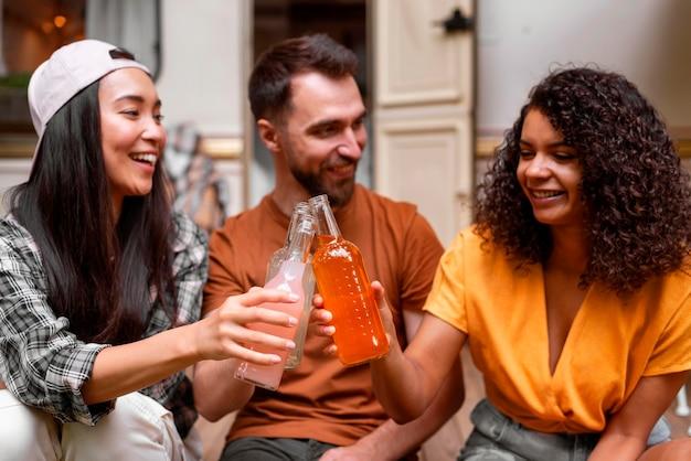 Felices tres amigos brindando por sus bebidas