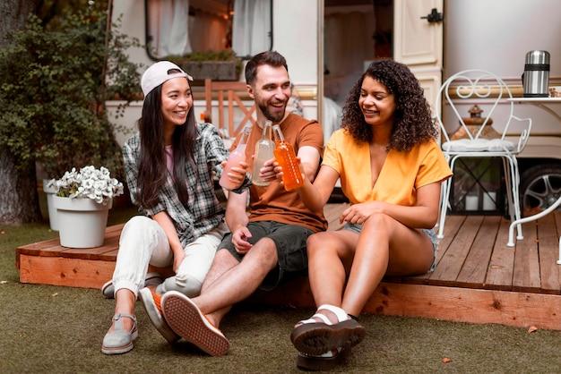 Felices tres amigos sentados y compartiendo bebidas