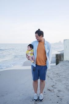 Felices vacaciones familiares asiáticas, un padre sostiene a su lindo bebé en la playa en verano, él mira a su bebé, viaje familiar por mar