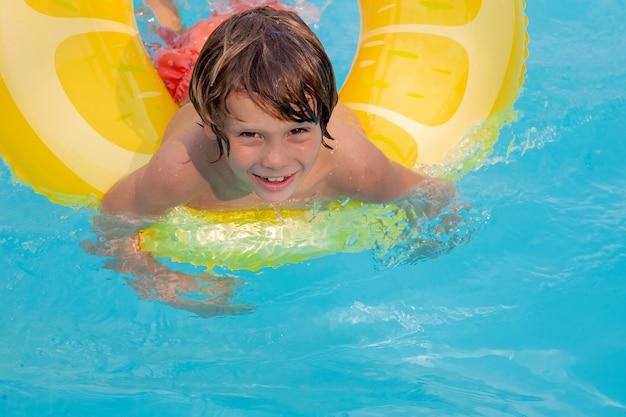 Felices vacaciones. niño divirtiéndose en la piscina con flotador. enfréntate a las emociones. vibras de verano.