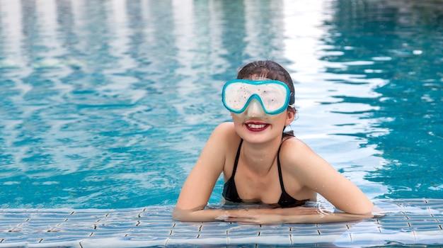 Felices vacaciones en la piscina de agua con gafas de buceo