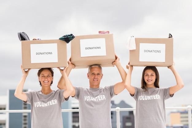 Felices voluntarios llevando cajas de donación en su cabeza