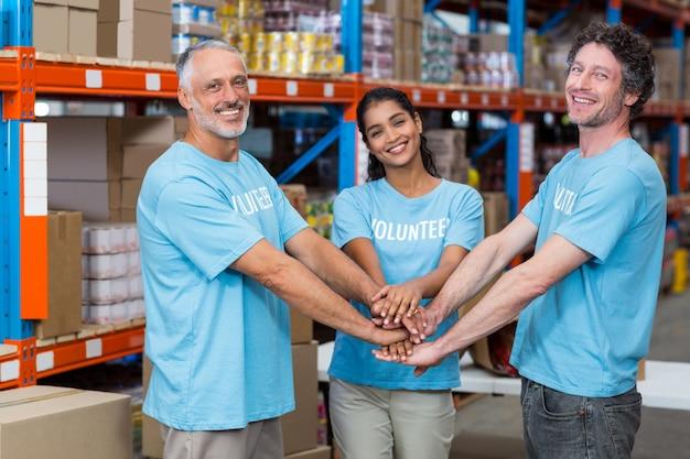 Felices voluntarios unen sus manos y miran la cámara