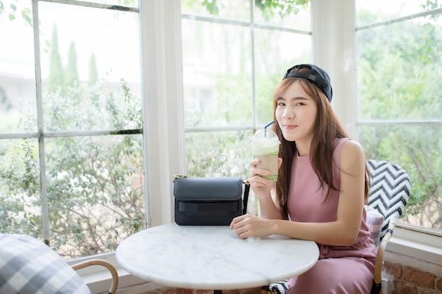 Felicidad cara sonriente de mujer joven asiática con una botella fría de bebida de té verde