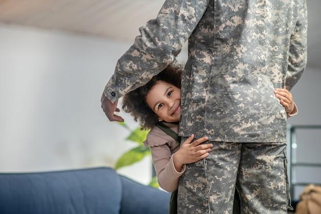 Felicidad. linda niña feliz con cabello rizado oscuro abrazando a papá en uniforme militar de pie en casa en la habitación
