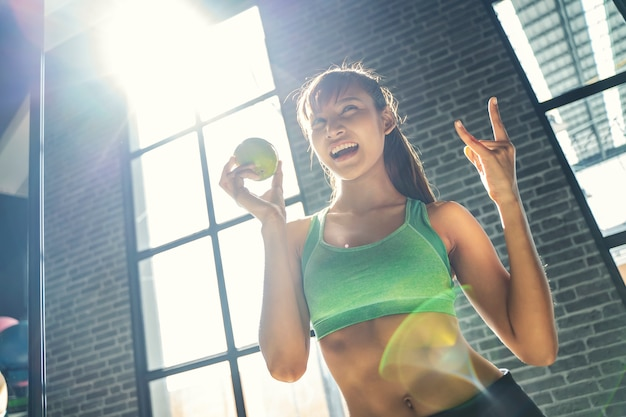 Felicidad y mujer deportiva con manzana verde con momento emocionado en el gimnasio