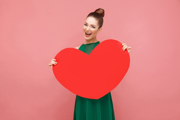 Felicidad mujer sosteniendo gran corazón rojo, dentudo sonriendo. concepto de emoción y sentimientos de expresión. foto de estudio, aislado sobre fondo rosa