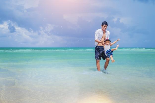 Felicidad papá e hijo jugando juntos en la playa tropical de verano.