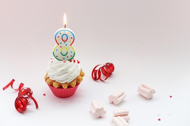 Felicitaciones por el día internacional de la mujer el 8 de marzo, pastel de crema y el número ocho sobre un fondo blanco.