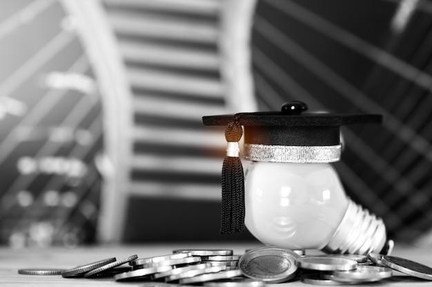 Felicitaciones a los graduados en las pilas de monedas en la mesa de madera