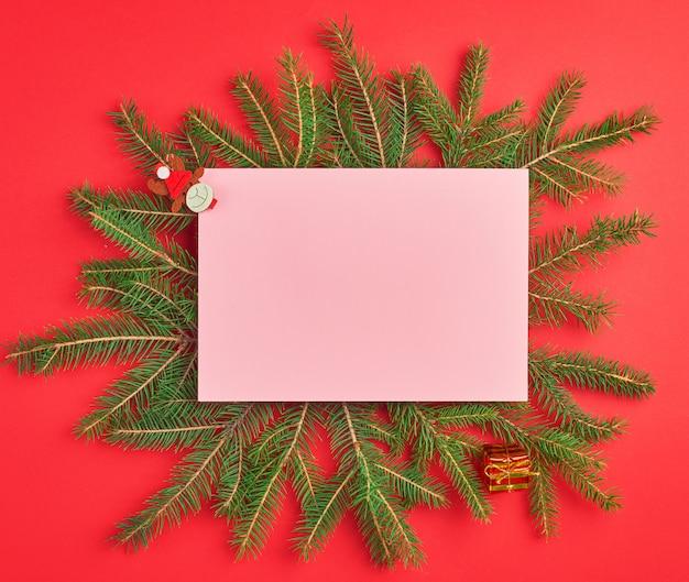 Felicitaciones de navidad de fondo con una sábana rosa vacía y ramas verdes
