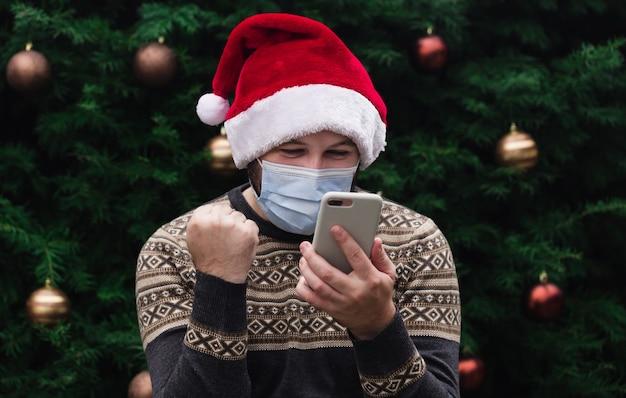 Felicitaciones de navidad en línea. hombre alegre con gorro de papá noel y máscara médica hablando por teléfono con amigos y padres. bokeh de árbol de navidad en el fondo