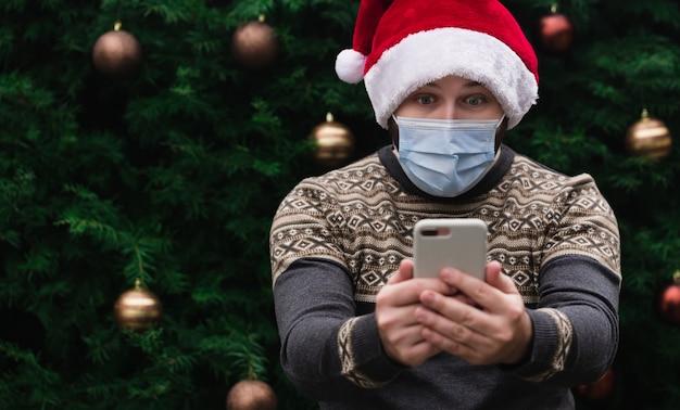 Felicitaciones de navidad en línea. hombre sorprendido, consternado con gorro de papá noel y máscara médica hablando por teléfono con amigos y padres. bokeh de árbol de navidad en el fondo