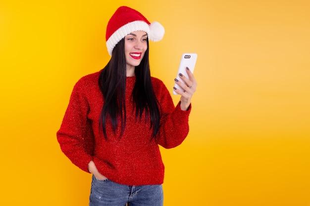 Felicitaciones de navidad en línea. mujer con sombrero de santa con tableta móvil para videollamadas a amigos y padres.