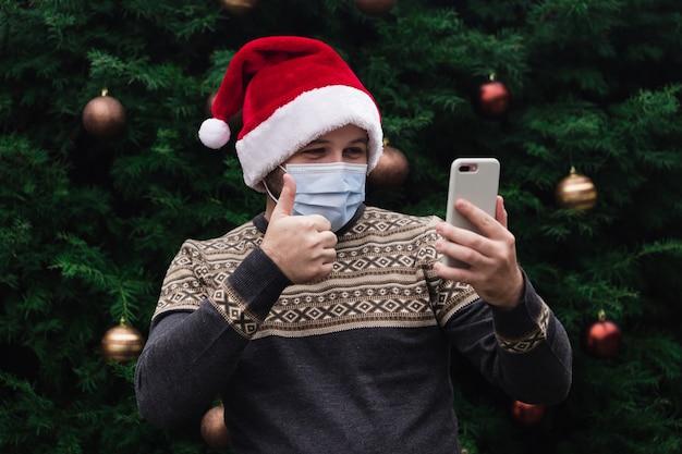 Felicitaciones de navidad en línea. retrato hombre feliz mostrando el pulgar hacia arriba, vistiendo gorro de papá noel y máscara médica. bokeh de árbol de navidad en el fondo