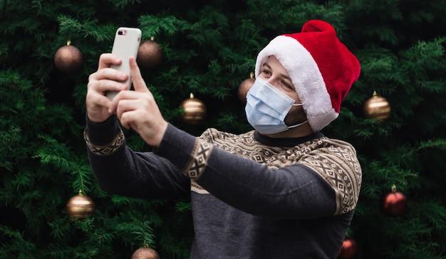 Felicitaciones de navidad en línea. retrato de hombre vestido con gorro de papá noel y máscara médica hablando por teléfono con amigos y padres. bokeh de árbol de navidad en el fondo