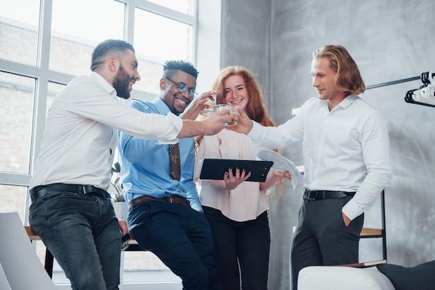Felicitaciones, nuestro plan de negocios es exitoso. los empleados de oficina pasan un buen rato celebrando sus logros.