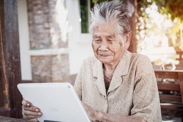 Feliz abuela anciana asiática sonriendo y usando tableta