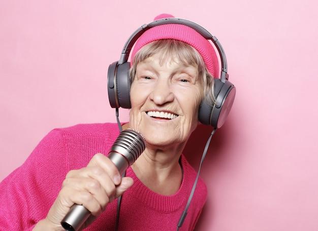Feliz abuela con auriculares y micrófono sobre fondo rosa, cantante gracioso