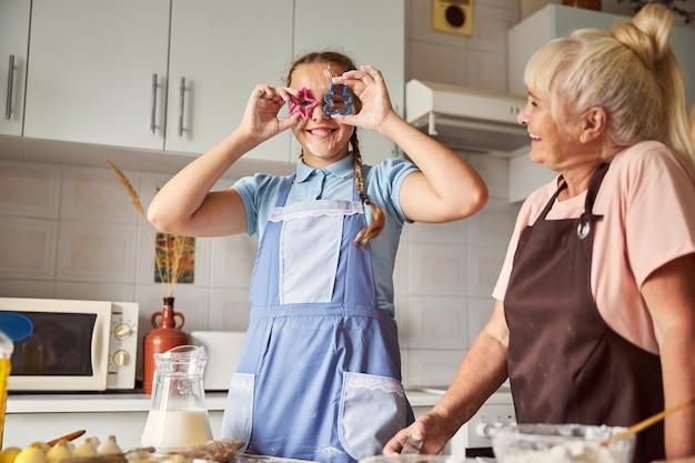 Feliz abuela y nieta encantadora que se divierten cocinando
