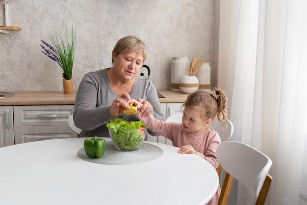 Feliz abuela y nieta preparan ensalada juntos en la cocina ligera. familia cocinando comida sana.