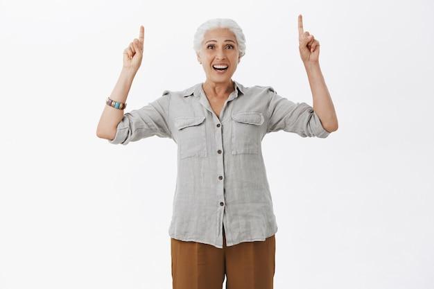 Feliz abuela sonriente entusiasta mirando divertido y señalando con el dedo hacia arriba