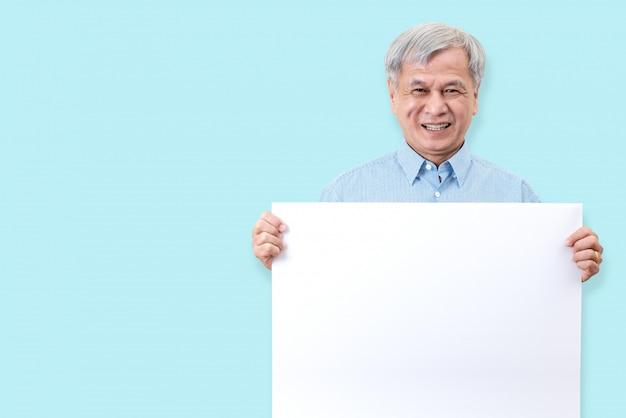 Feliz abuelo sonriendo con dientes blancos, disfruta del momento y sosteniendo una tabla en blanco.