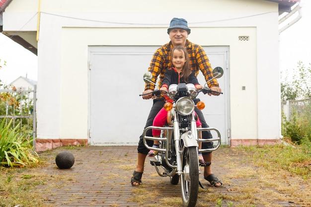 Feliz abuelo y su nieta en bicicleta sidecar hecha a mano sonriendo